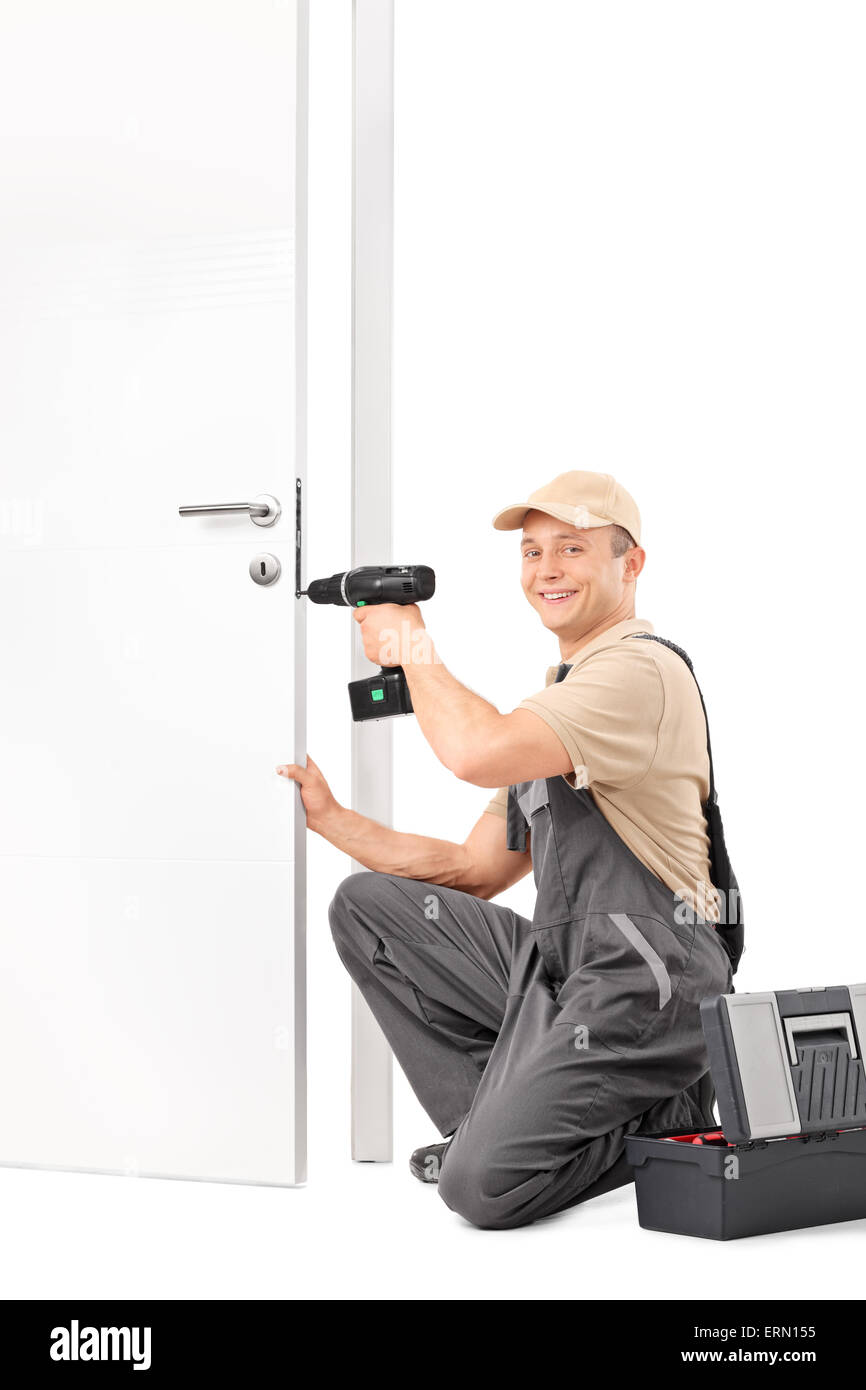 Vertical shot of a young locksmith screwing a lock on a door with a hand drill and looking at the camera - Stock Image