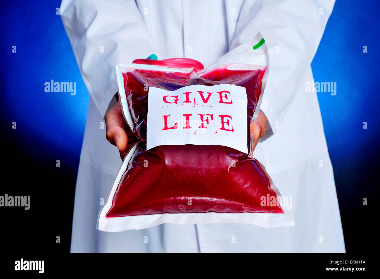 closeup of a doctor showing a blood bag with a sticker with the text give life - Stock Image