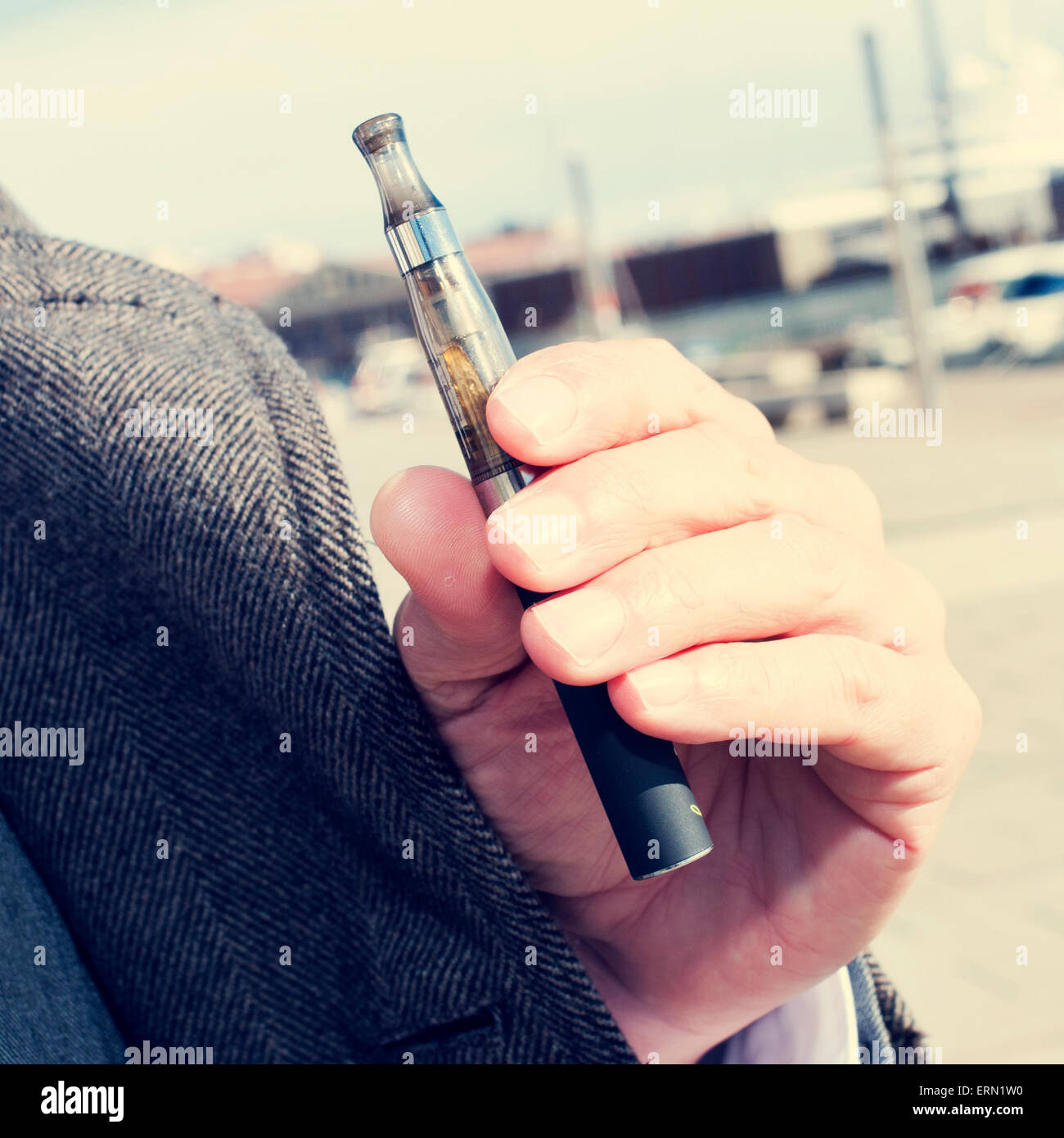 closeup of the hand of a young caucasian man vaping with an electronic cigarette outdoors - Stock Image