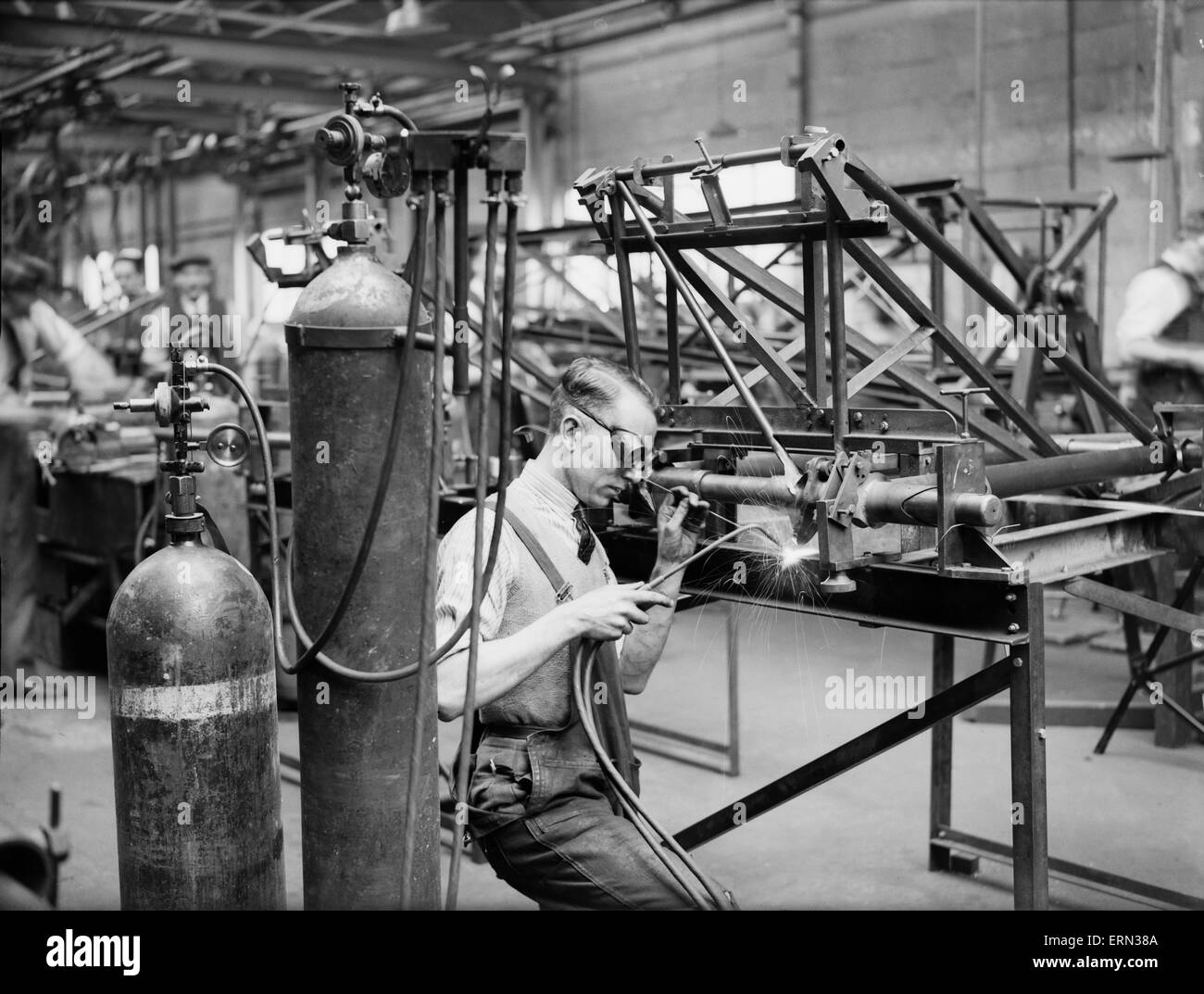A welder constructs the fuselage framework of the Miles 3 Falcon aircraft at the Philips and Powis factory at Woodley - Stock Image