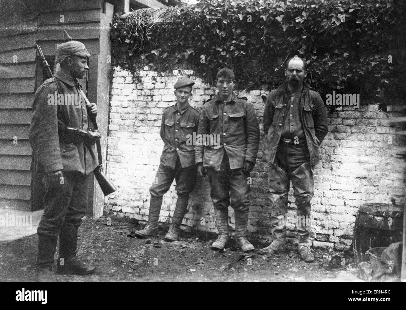 A German soldier guards three recently captured British soldiers April 1917 - Stock Image