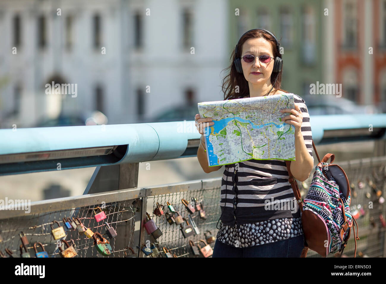 Young female tourist, standing on the pedestrian bridge with locks of love, with map looking for the direction. - Stock Image