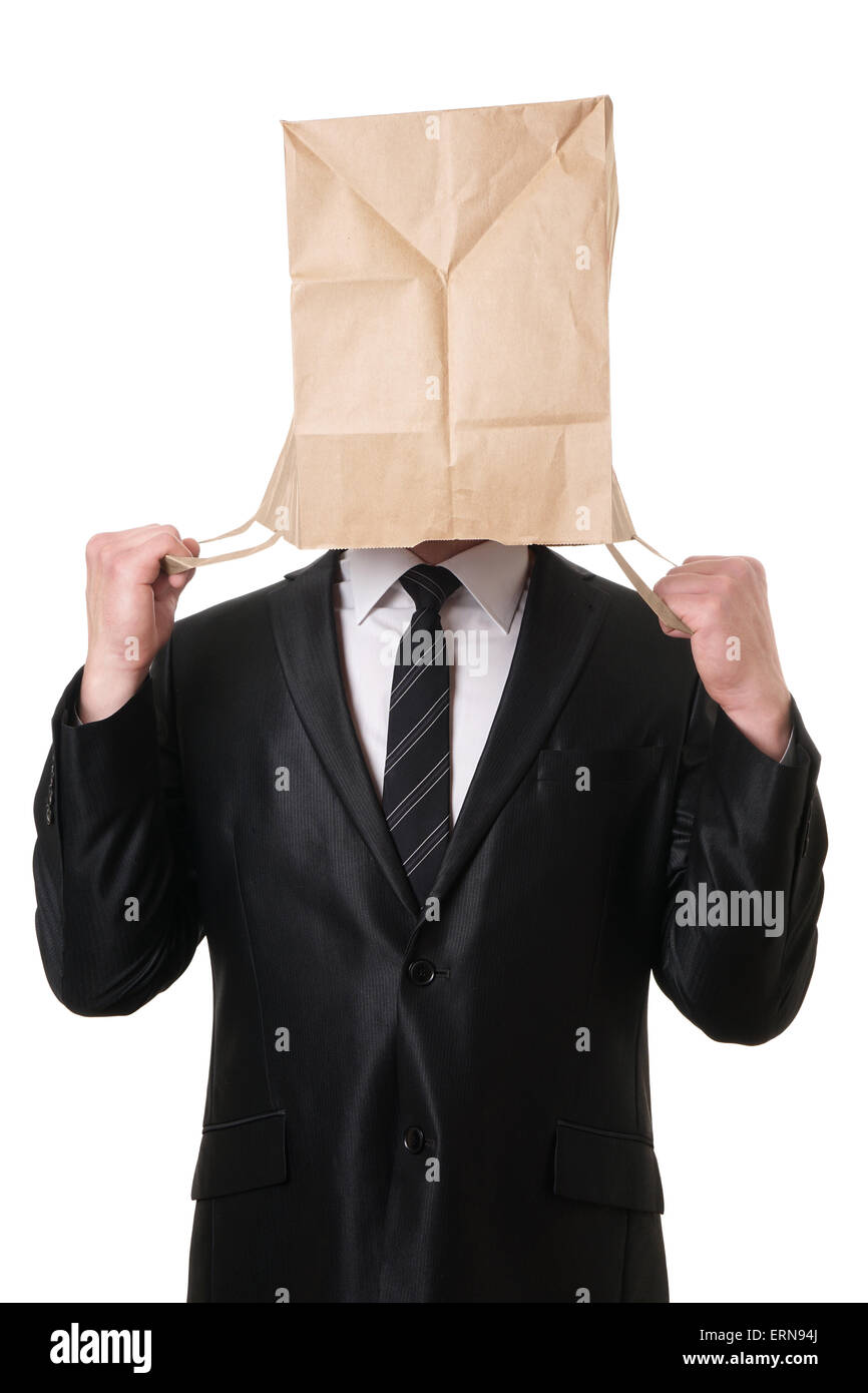 businessman pulling paper bag over his head - Stock Image
