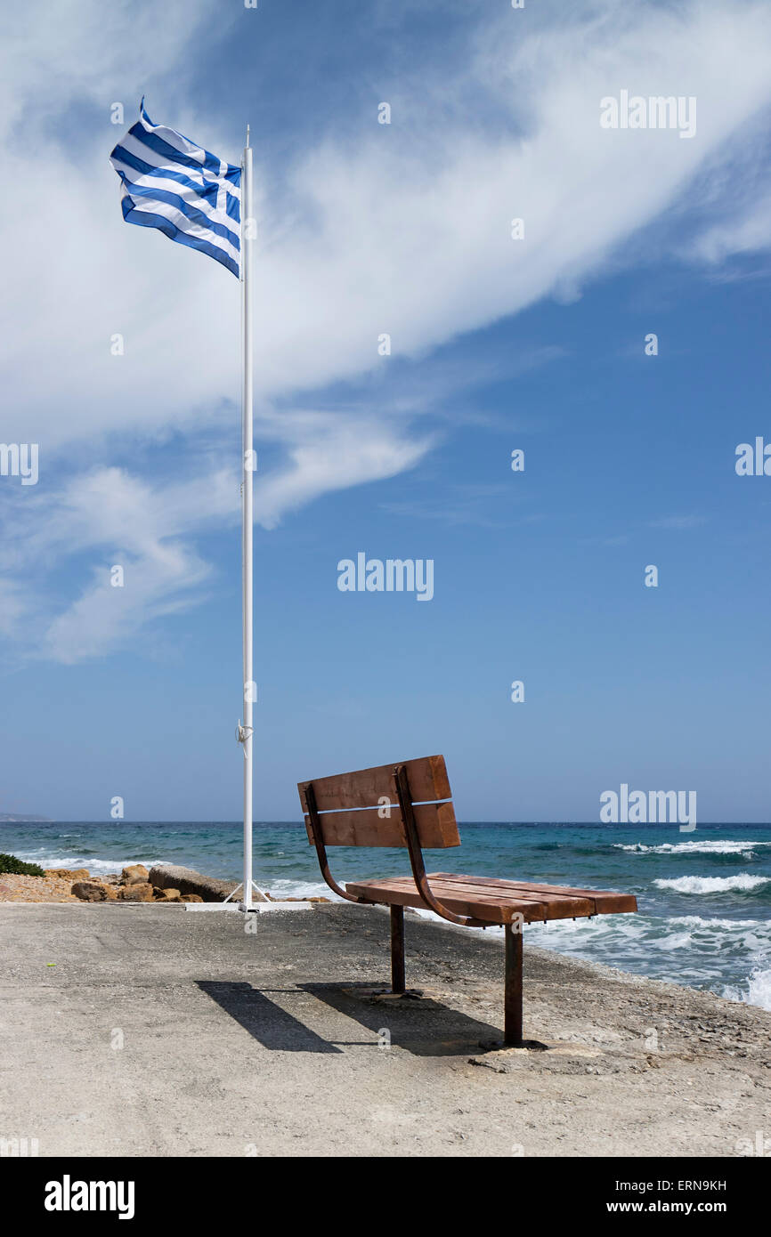 Greek banner and empty bench on the beach in Mega Limnionas on the isle of Chios, Greece - Stock Image