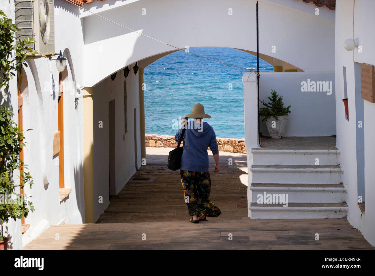 Tourist walking to the sea in Mega Limnionas on the isle of Chios, Greece - Stock Image