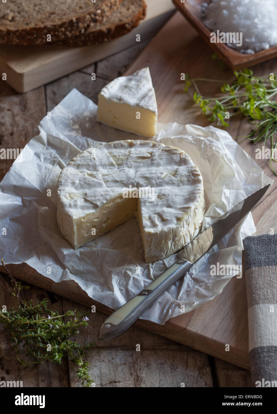 A piece of camembert cheese on a cutting board with a knife and herbs. - Stock Image