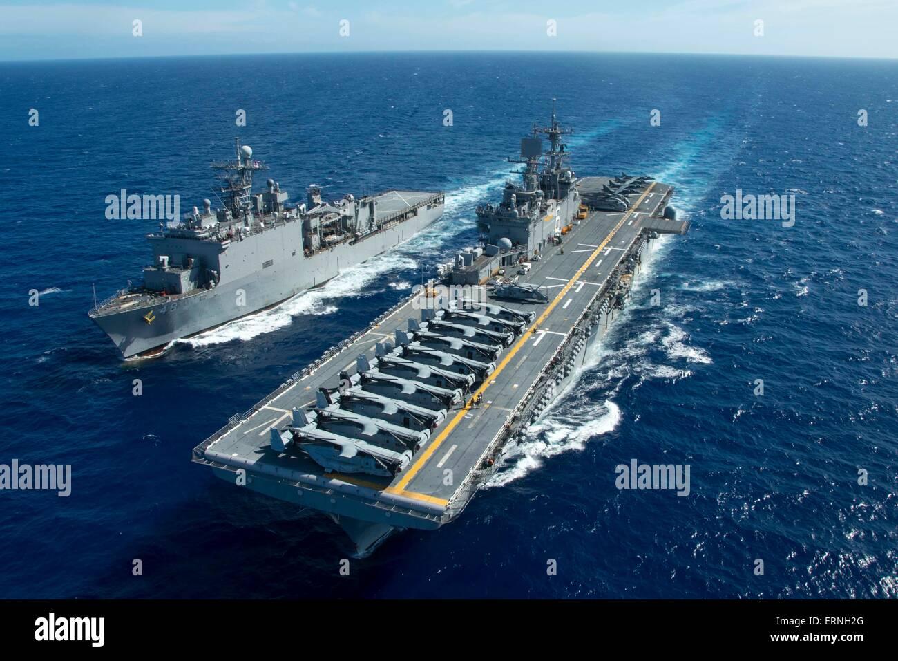 US Navy amphibious assault ship USS Bonhomme Richard and USS Ashland maneuver to conduct a replenishment at Sea Stock Photo