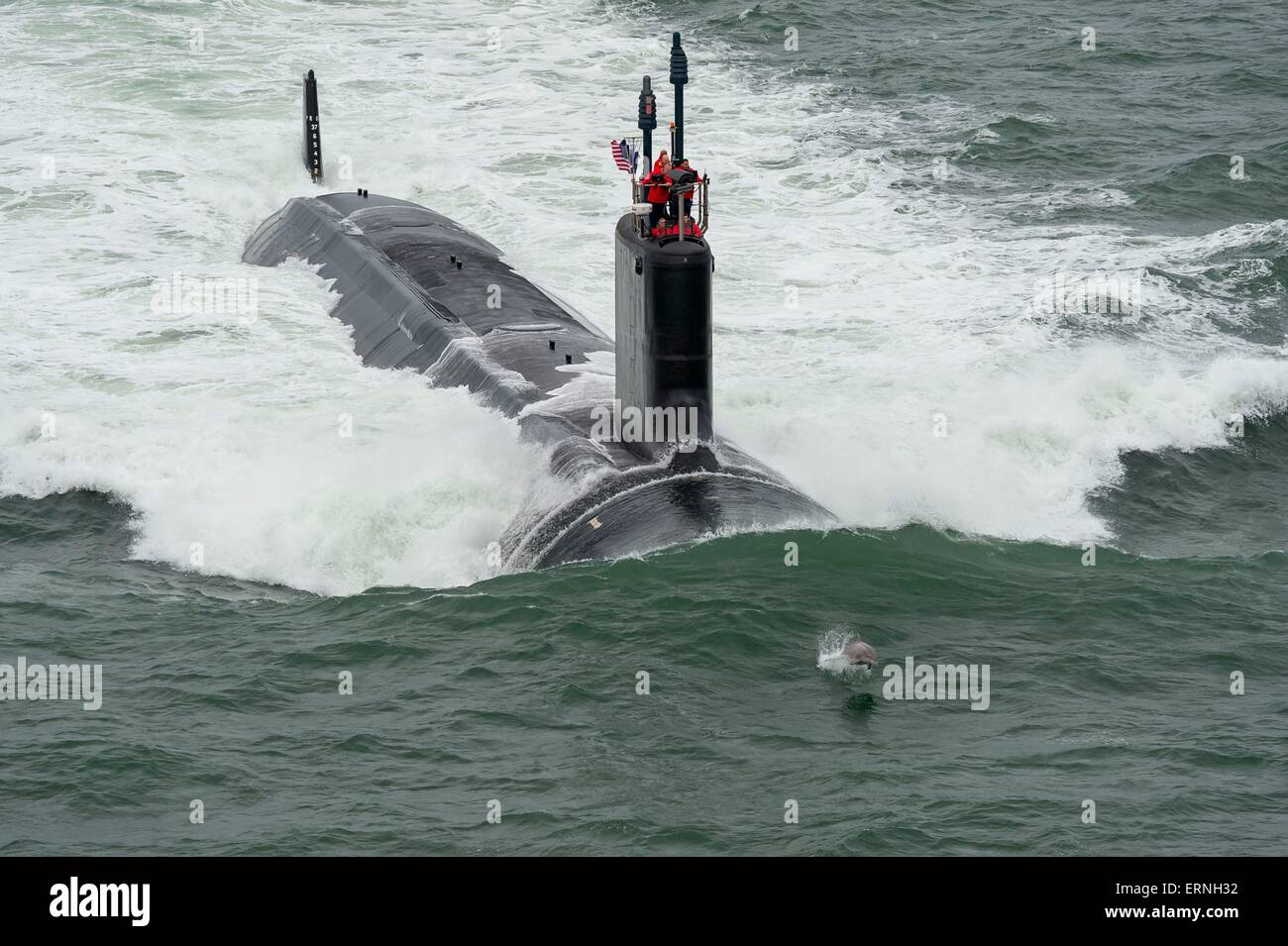 A dolphin jumps in front of the Virginia-class attack submarine USS John Warner as the boat conducts sea trials - Stock Image