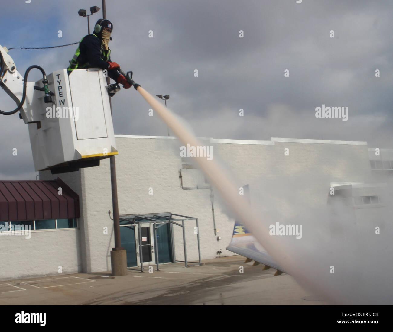 worker de-icing commercial airliner wing Cincinnati Ohio - Stock Image