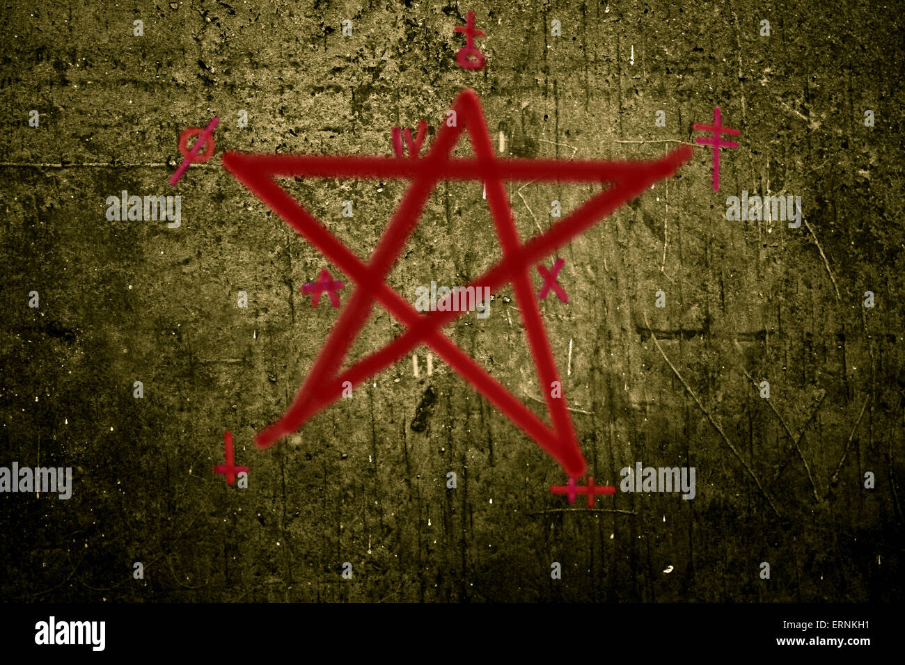 Altered photo of a red pentagram with symbols on a rough concrete wall - Stock Image