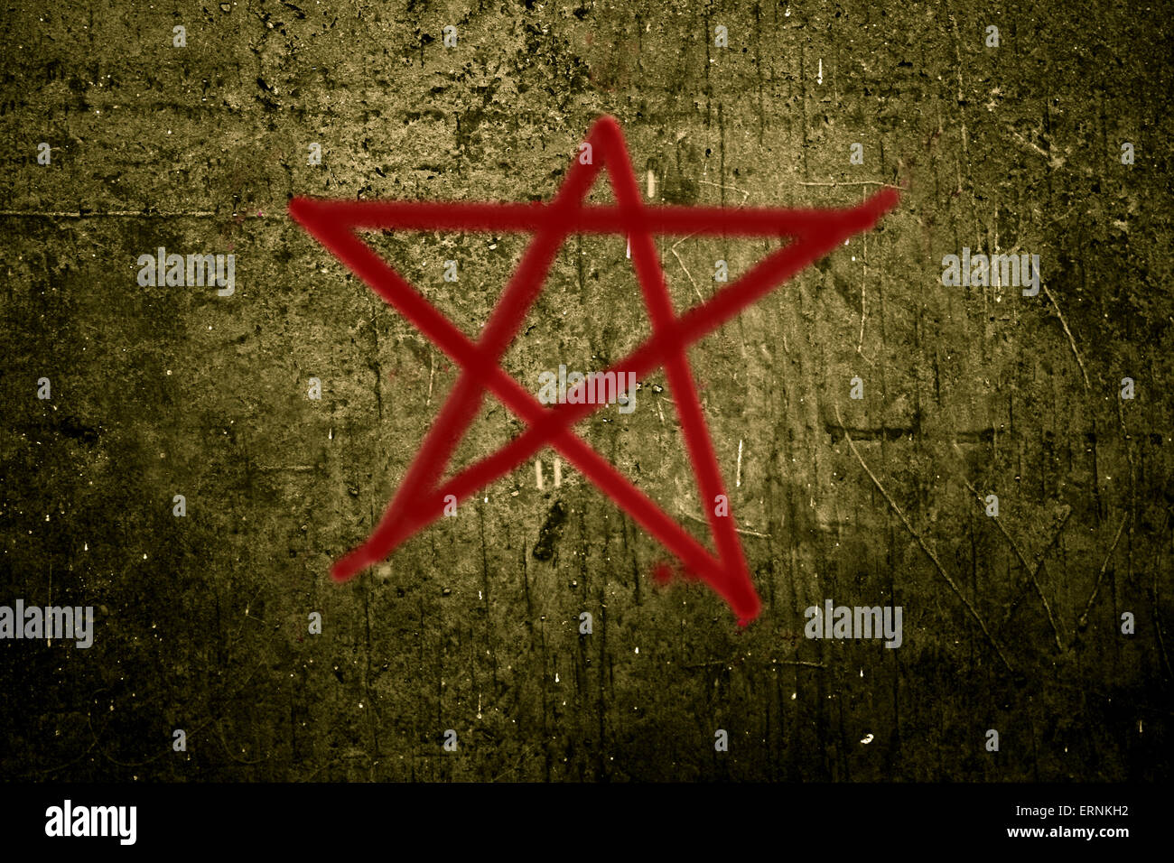 Altered photo of a red pentagram on a rough concrete wall - Stock Image