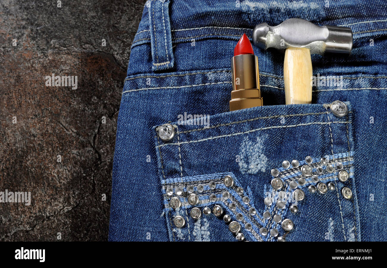 Female worker blue jeans with rhinestone decoration and red lipstick and hammer in back pocket for crafting or construction - Stock Image