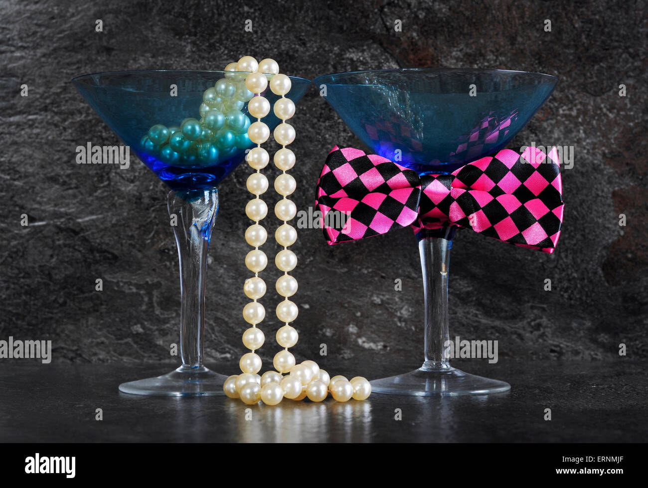 Ladies and Gentleman's vintage blue martini glasses with pearls and fun pink check bow tie  on black slate background. - Stock Image