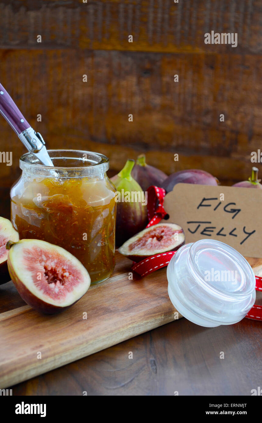 Fresh ripe Autumn fruit, figs, with fig jelly preserve in jar on cutting board against dark wood background. - Stock Image
