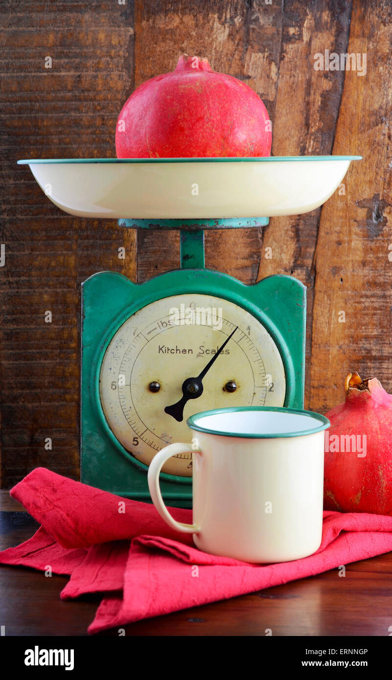 Vintage kitchen scales and tin cups and pans on dark reclaimed wood background. - Stock Image
