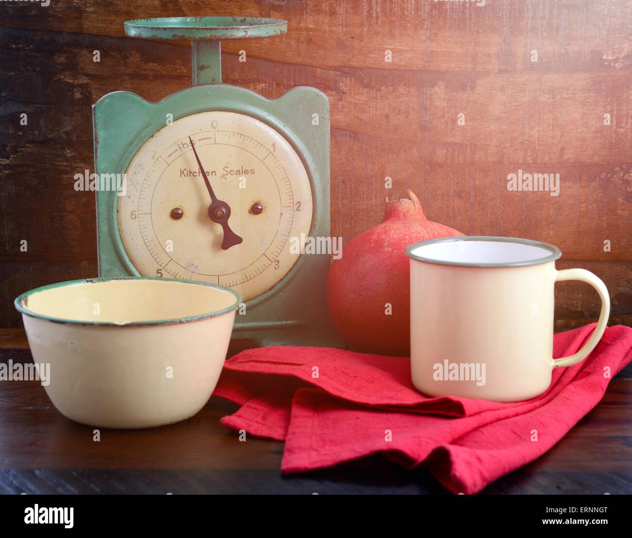 Vintage kitchen scales and tin cups and pans on dark reclaimed wood background, with applied vintage style filters - Stock Image