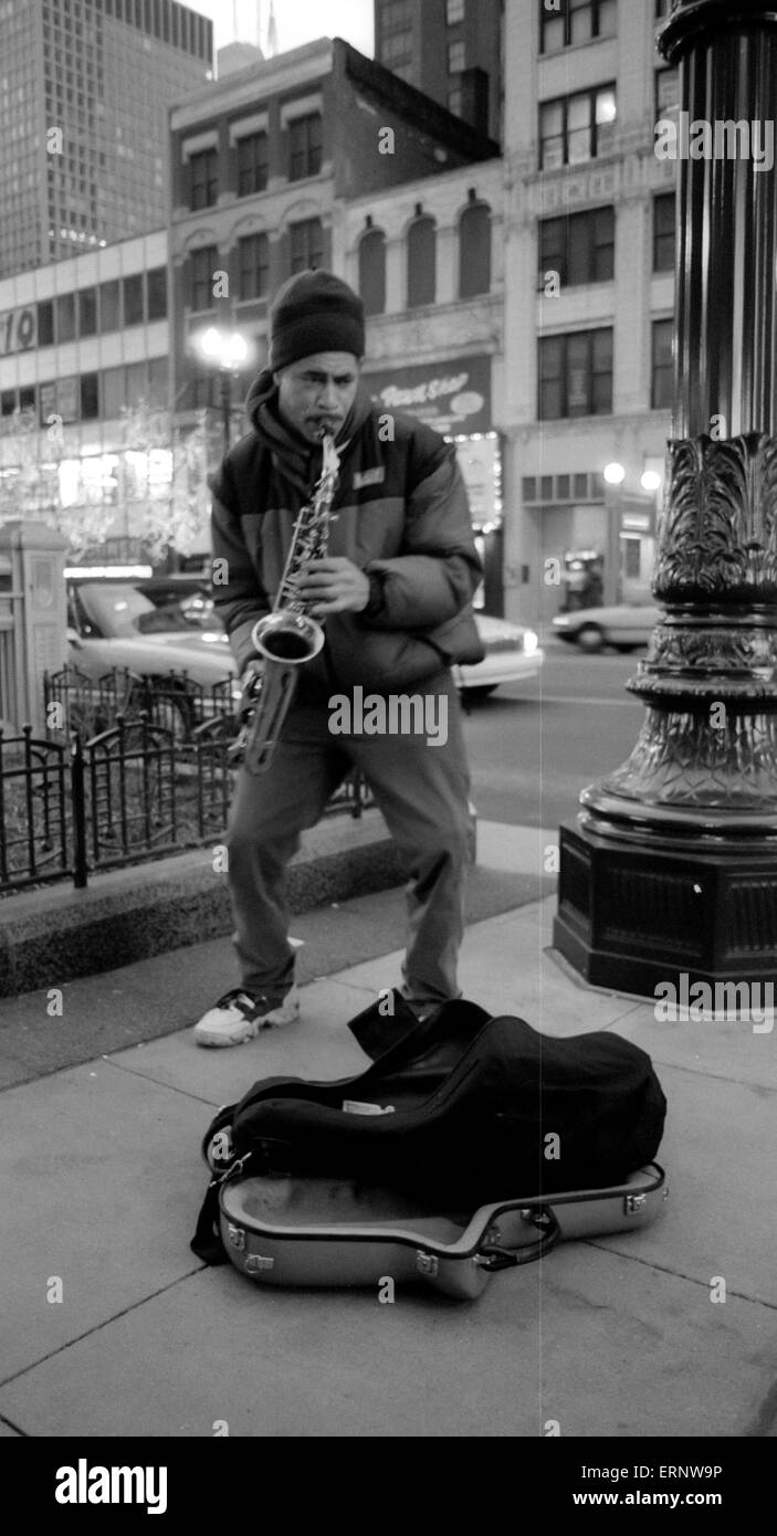 Chicago, IL, 14-Dec-1996: A street musician is playing the saxophone in front of the Chicago Theater on State St. - Stock Image