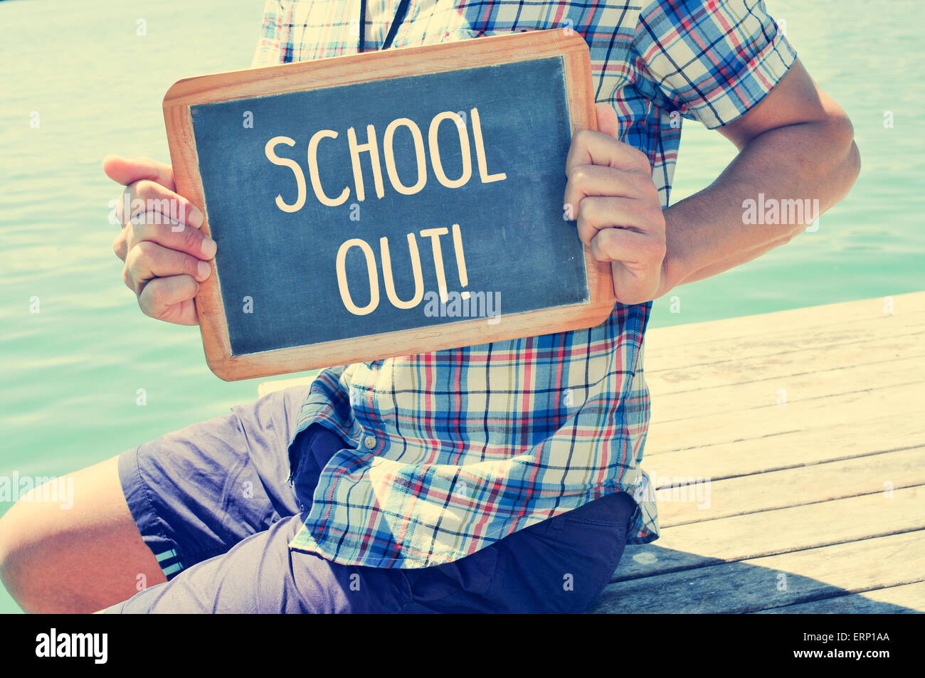a young caucasian man sitting in a wooden pier shows a chalkboard with the text schools out written in it, with - Stock Image