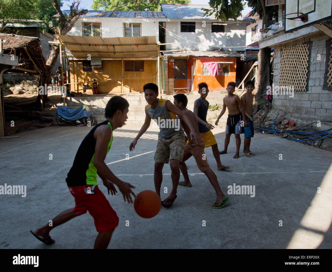 Youth playing basketball in a slum in Ilo Ilo, Philippines - Stock Image