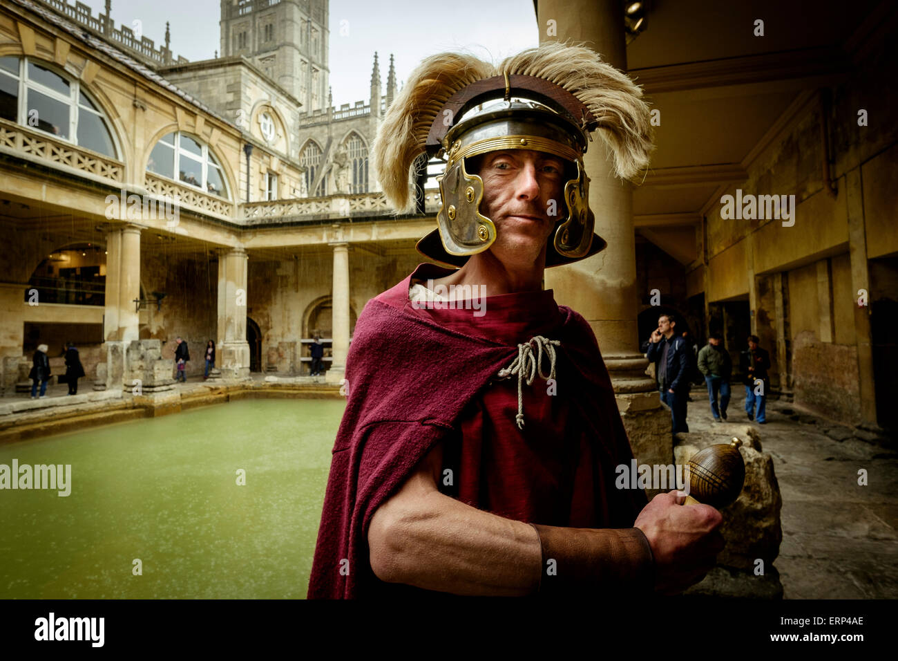In the Roman Baths at Bath, UK this costumed man acts as a guide and photo prop for those wishing to pose with a - Stock Image