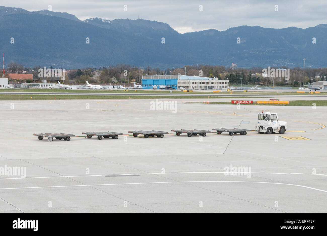 Empty baggage trolleys at Geneva airport being towed across the taxiway or apron.  Concept lost or missing luggage - Stock Image