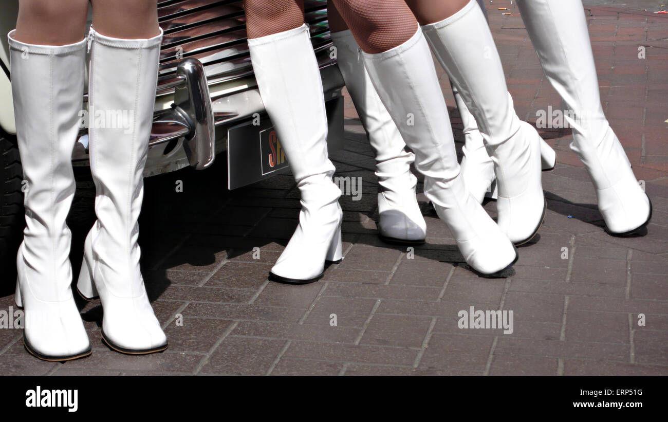 1960's style models in  white boots and union jack mini skirts in front of a classic white mini car Stock Photo