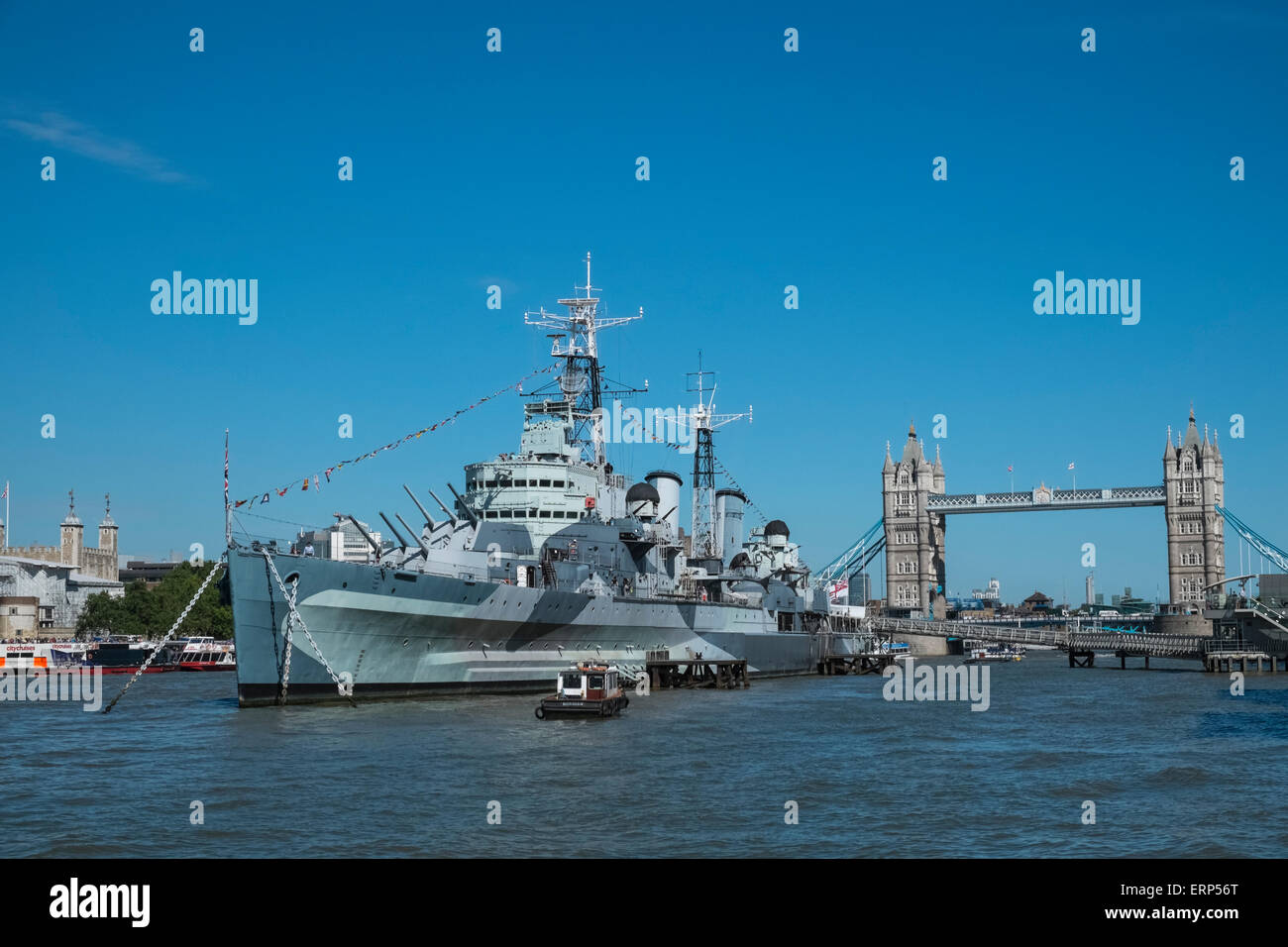 HMS Belfast museum ship moored on River Thames, with Tower Bridge in the background, London UK - Stock Image