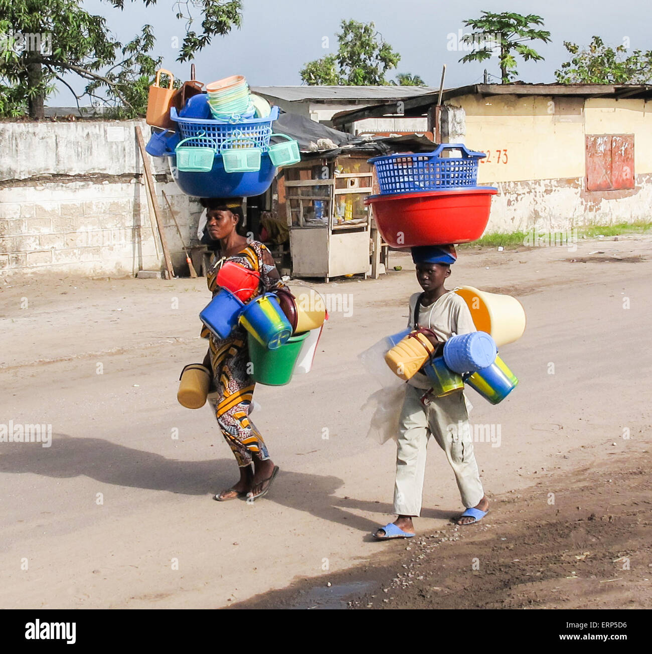 An African woman and child in Brazzaville the capital of the Republic of Congo carrying plastic water buckets on - Stock Image