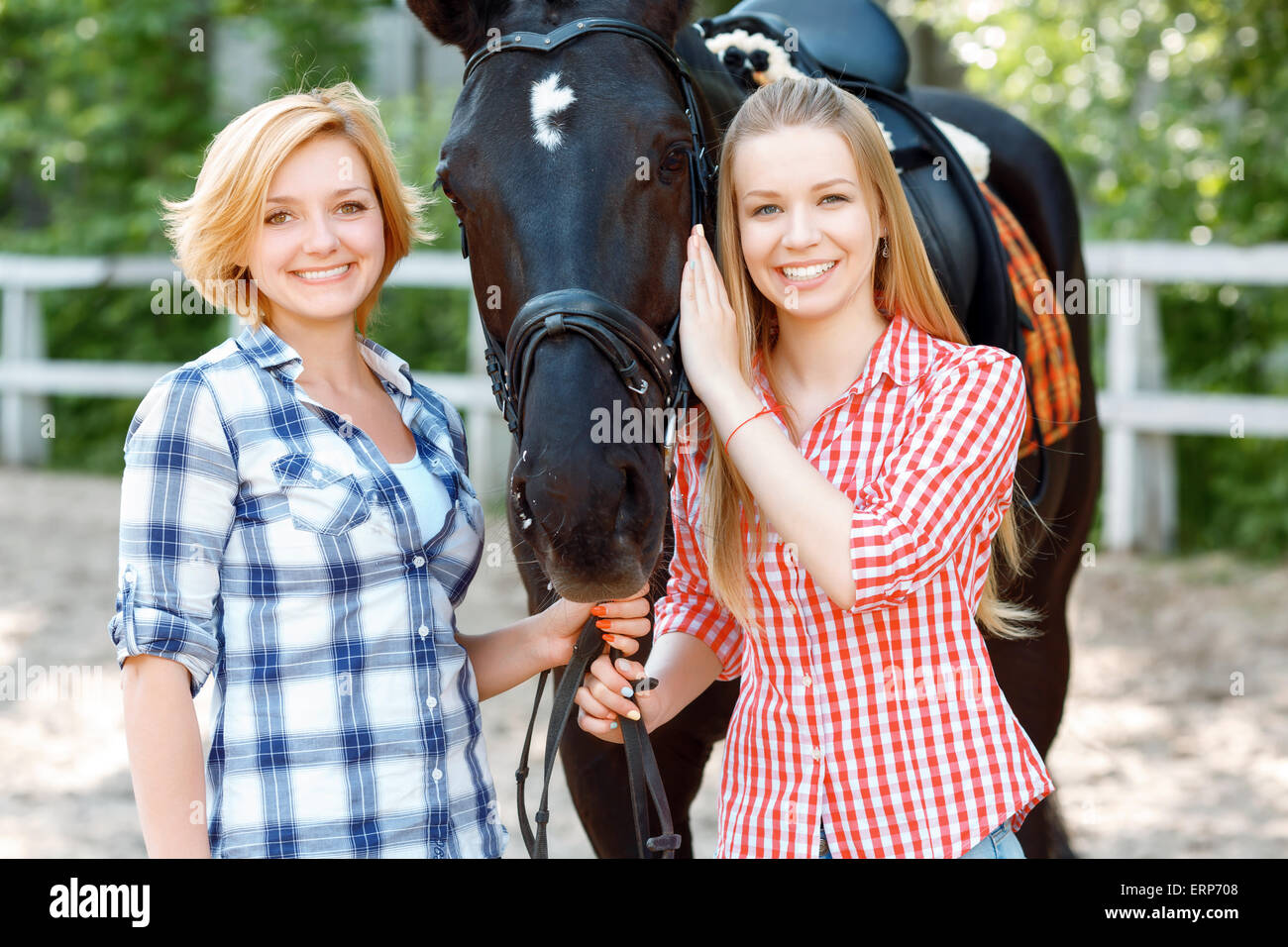 Happy sisters  standing with the horse Stock Photo