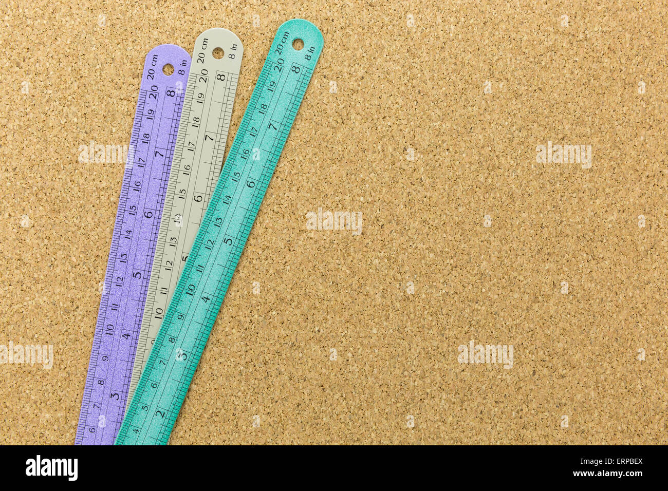 three color of rulers place on cork board with space - Stock Image