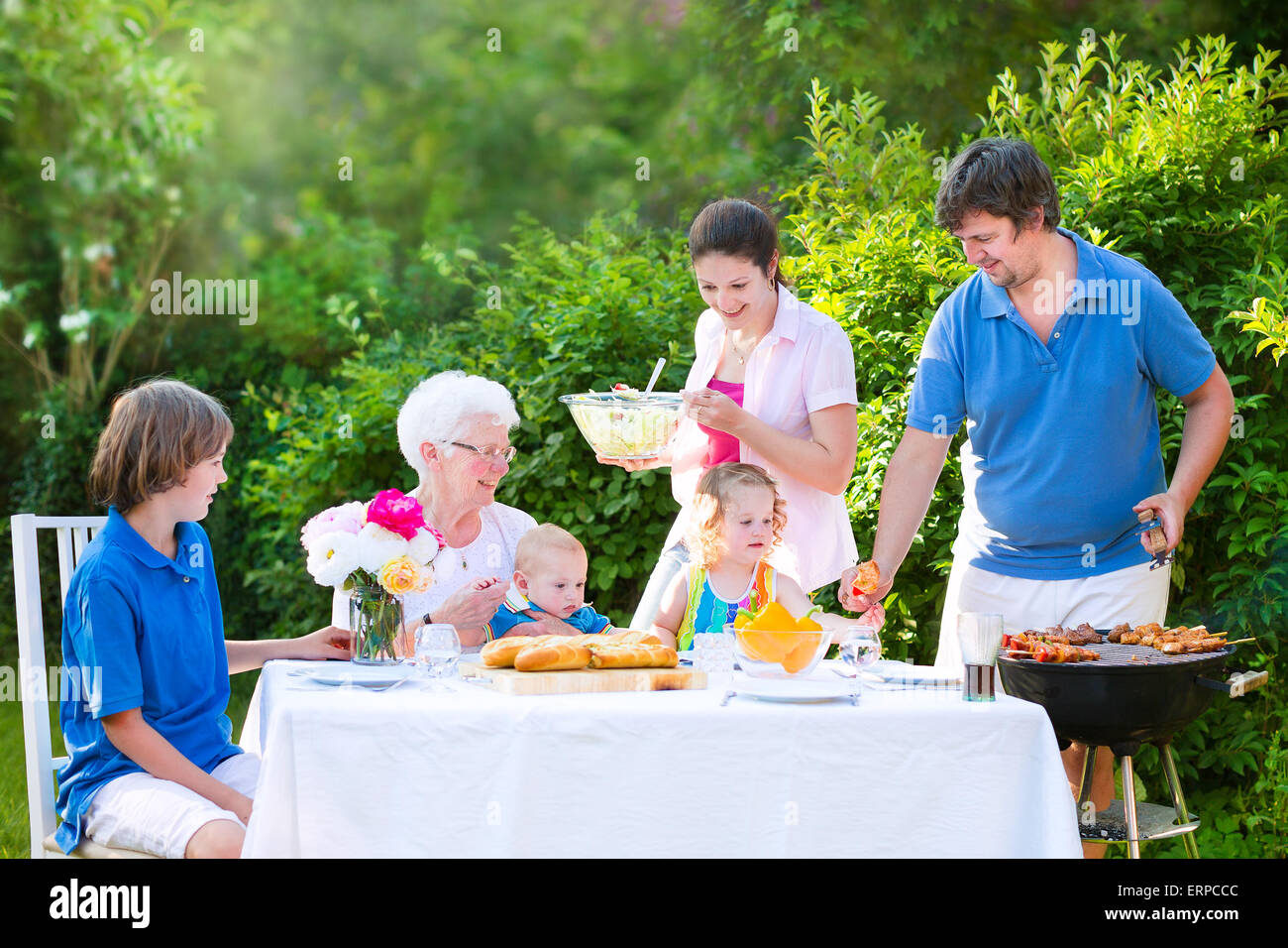 Grill barbecue backyard party. Happy big family enjoying BBQ lunch with grandmother eating meat in the garden with - Stock Image