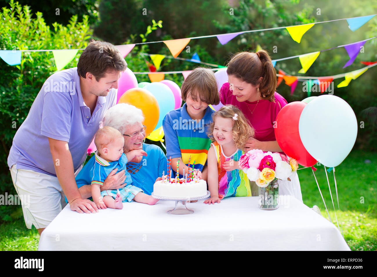 Big family with three kids and grandmother enjoying birthday party