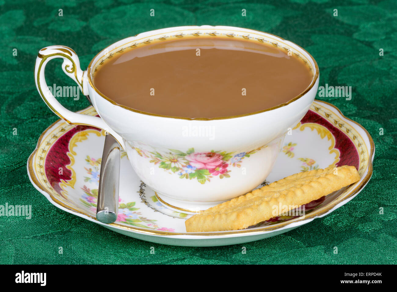 Cup of tea and a biscuit in a fine china cup with saucer. - Stock Image