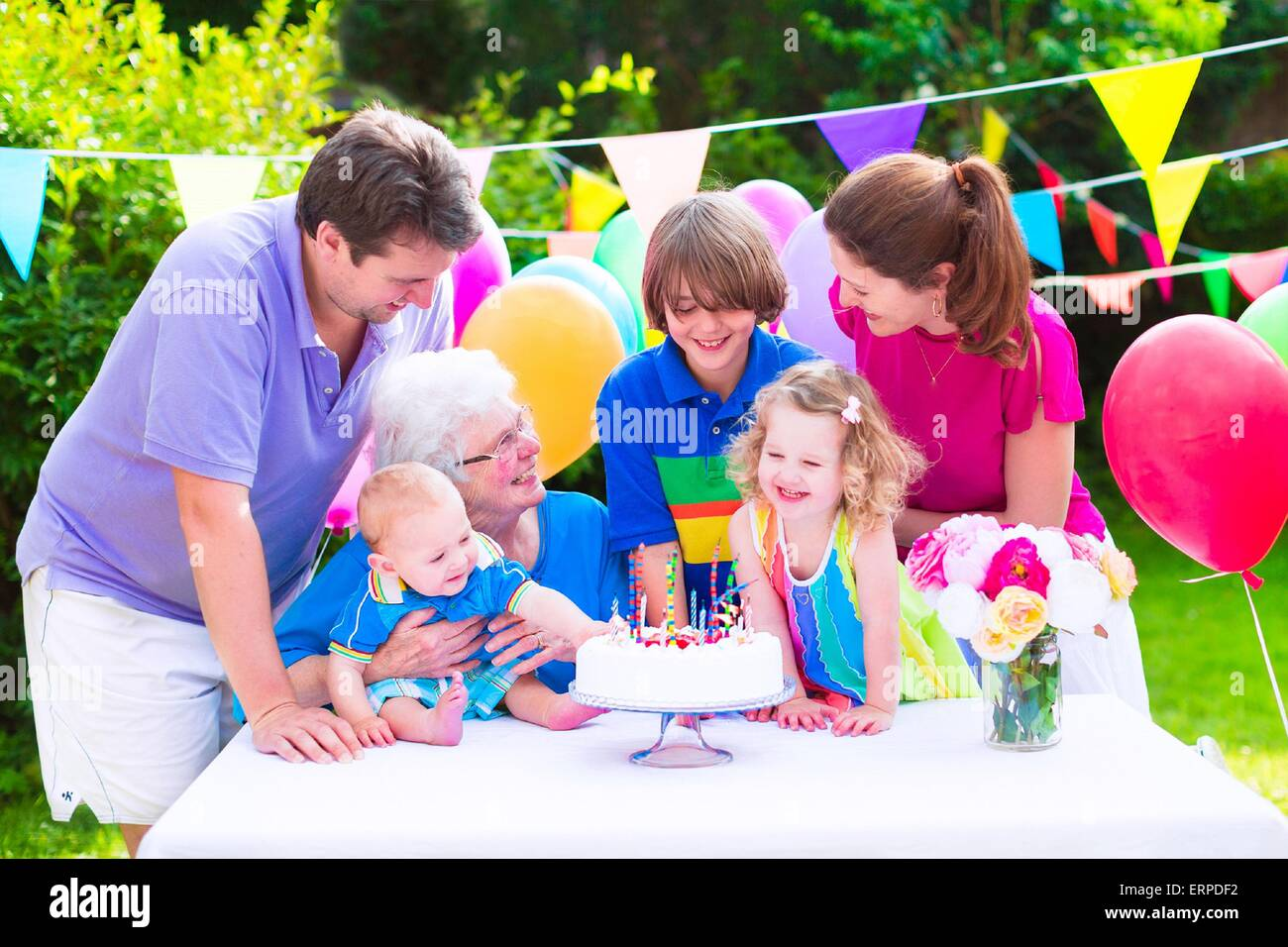 Big family with three kids and grandmother enjoying birthday party with cake blowing candles in garden decorated Stock Photo