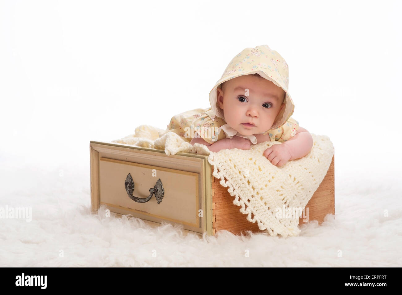 A 3 month old baby girl wearing a yellow bonnet and lying in a vintage  yellow drawer. f7f67039098