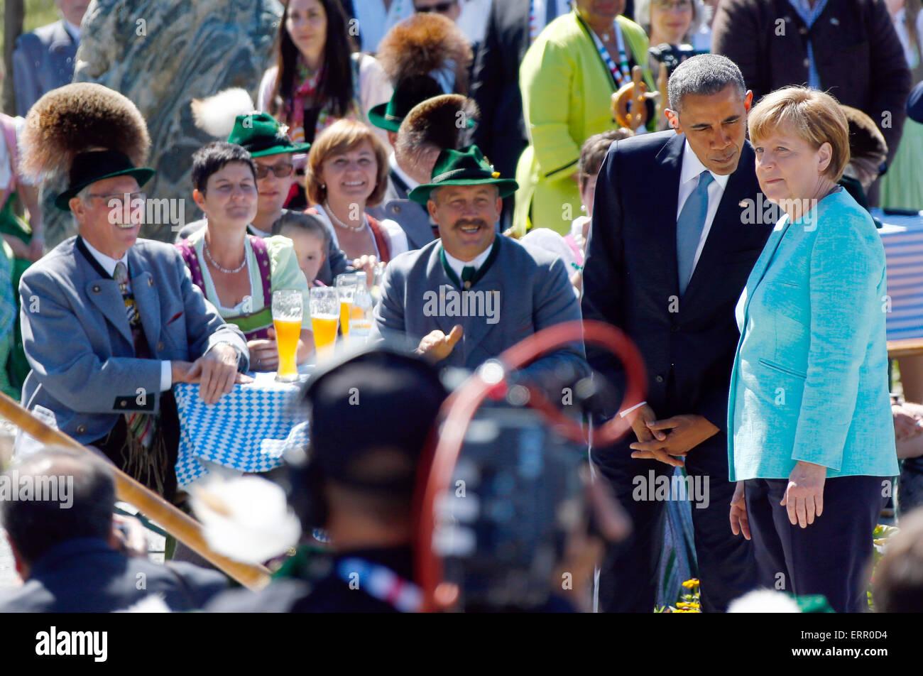 U.S. President Barack Obama talks to German Chancellor Angela Merkel, right, during a joint walk through the village of Kruen, southern Germany, Sunday, June 7, 2015 prior to the G-7 summit in Schloss Elmau hotel near Garmisch-Partenkirchen where the summit will start later the day. Photo: Matthias Schrader dpa Stock Photo