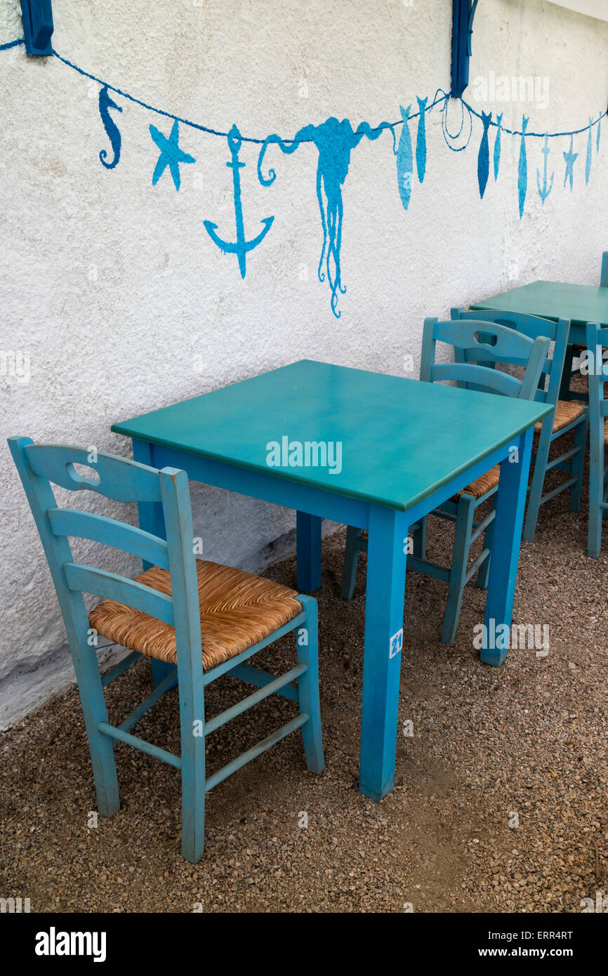 Empty restaurant with characteristic blue chairs,table and wall painting at the beach on the isle of Chios, Greece - Stock Image
