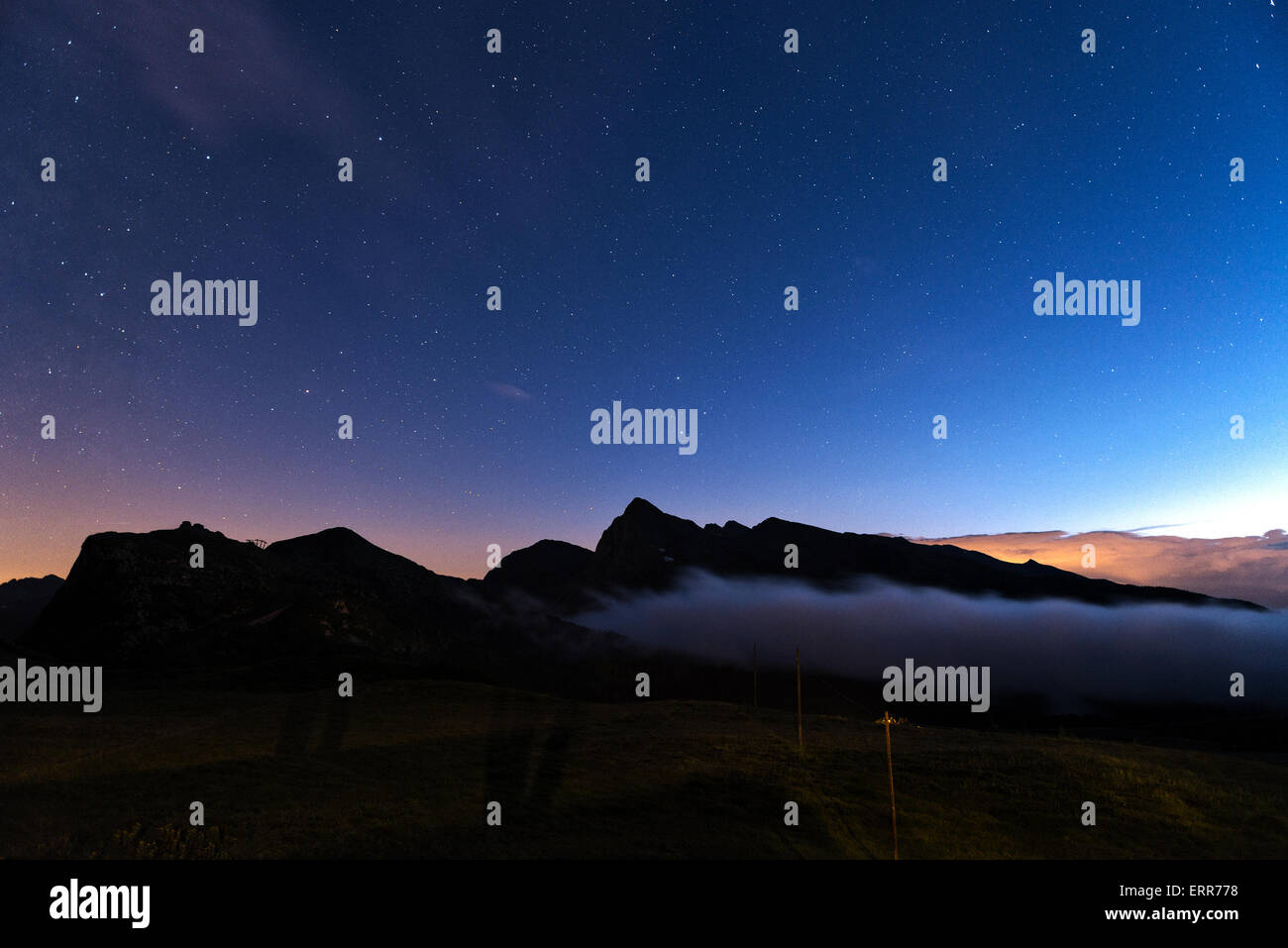 evening at the Rolle pass with fog on the mountains and blue sky with stars background, Trentino - Italy - Stock Image