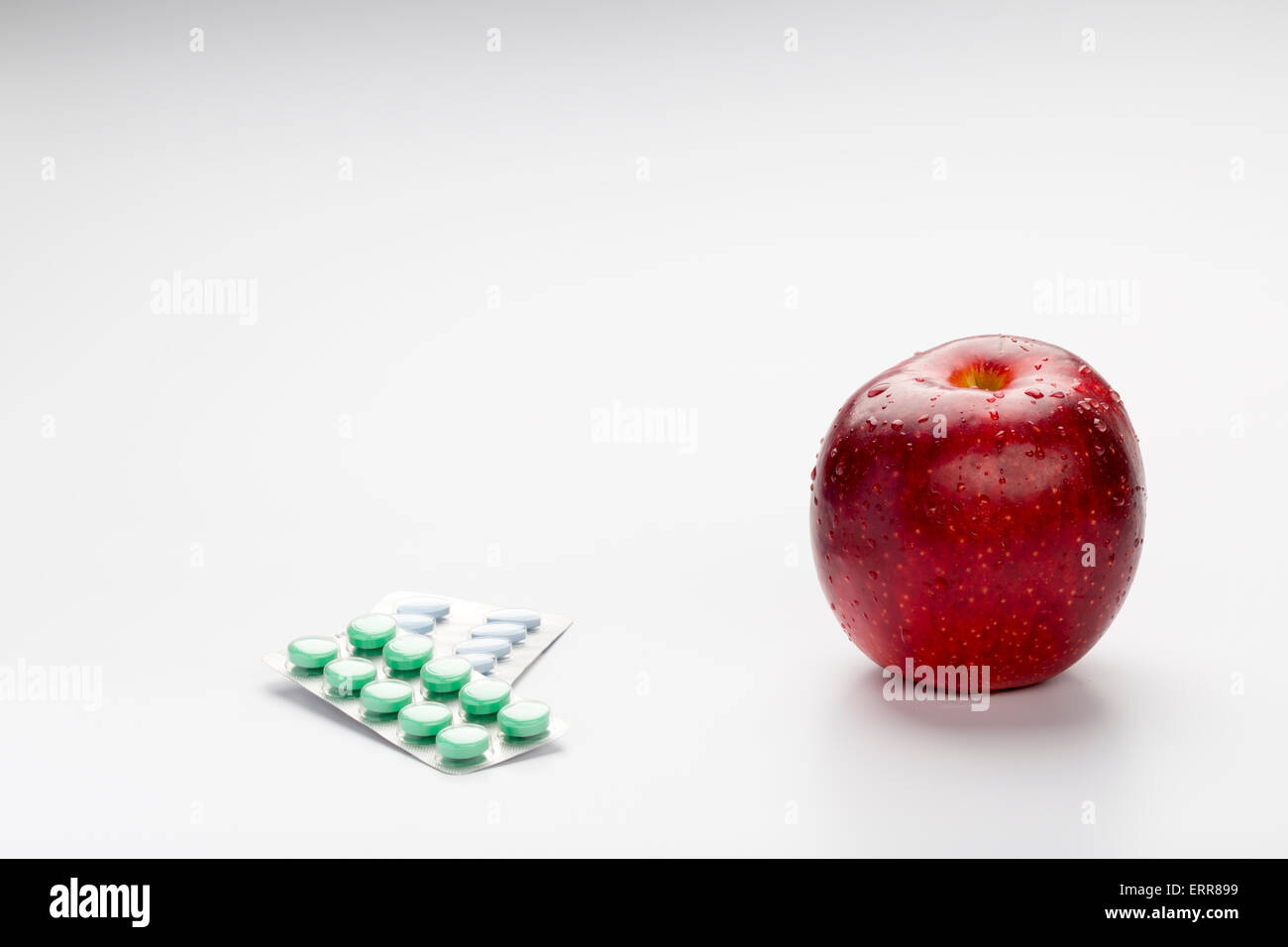 Red apple and colorful pills in blister on white background - Stock Image