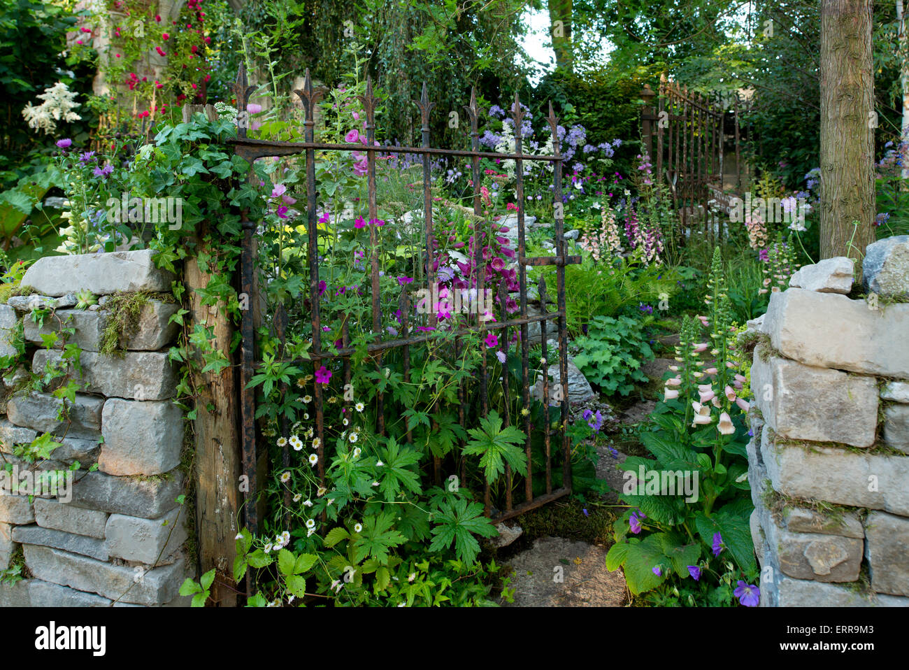 A stone wall and metal gate leading into The Forgotten Folly Garden at The Hampton Court Flower Show, 2014 - Stock Image