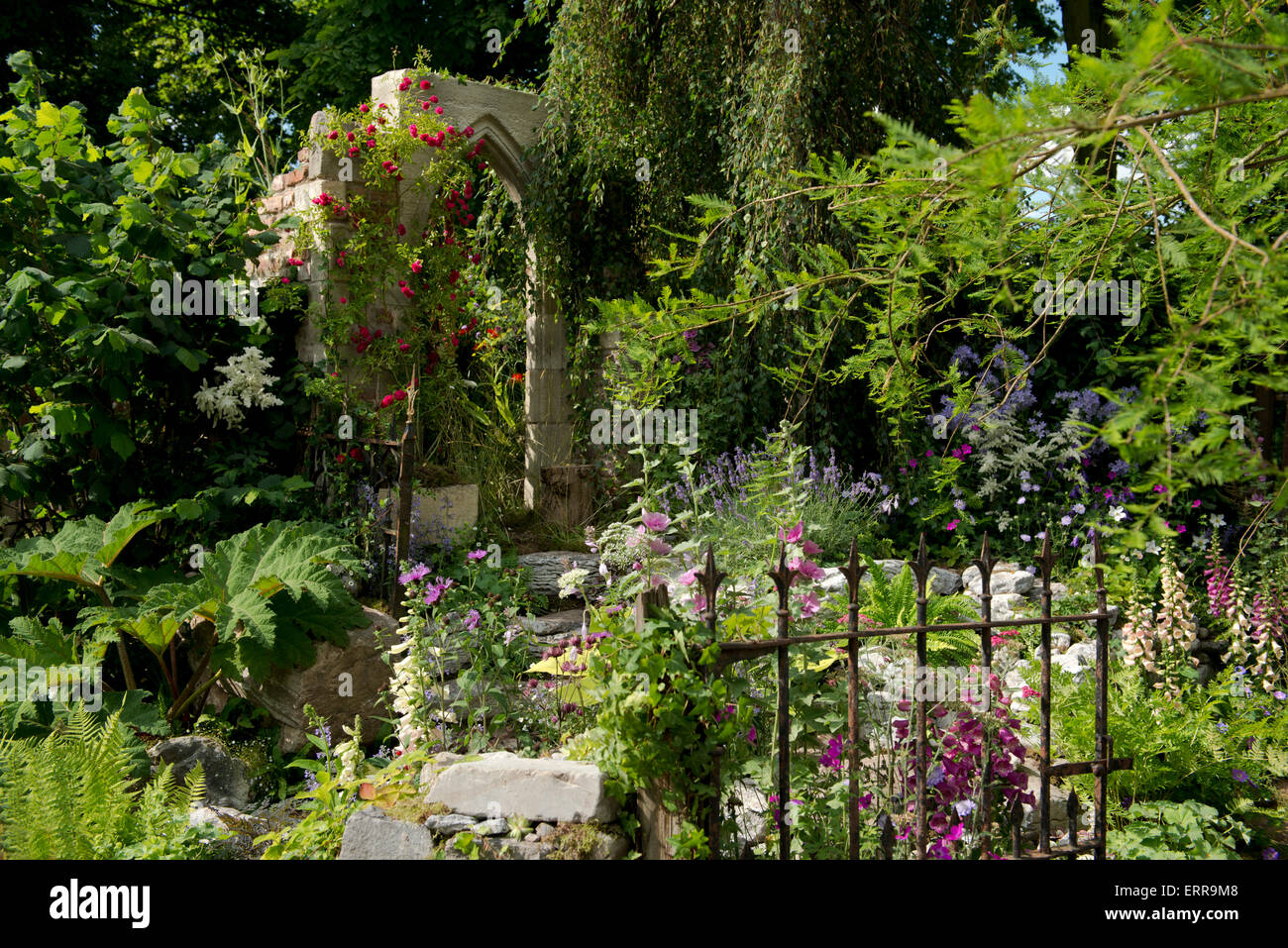 A stone arch surrounded by naturalistic planting in The Forgotten Folly Garden at The Hampton Court Flower Show, - Stock Image