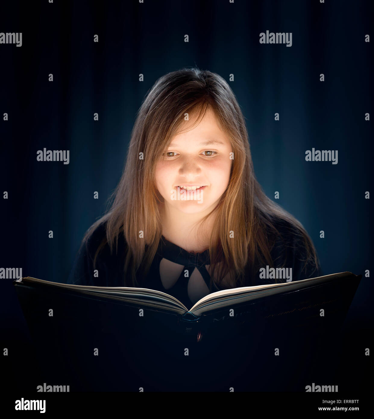 Young girl with long hair reading a book with glowing light - Stock Image