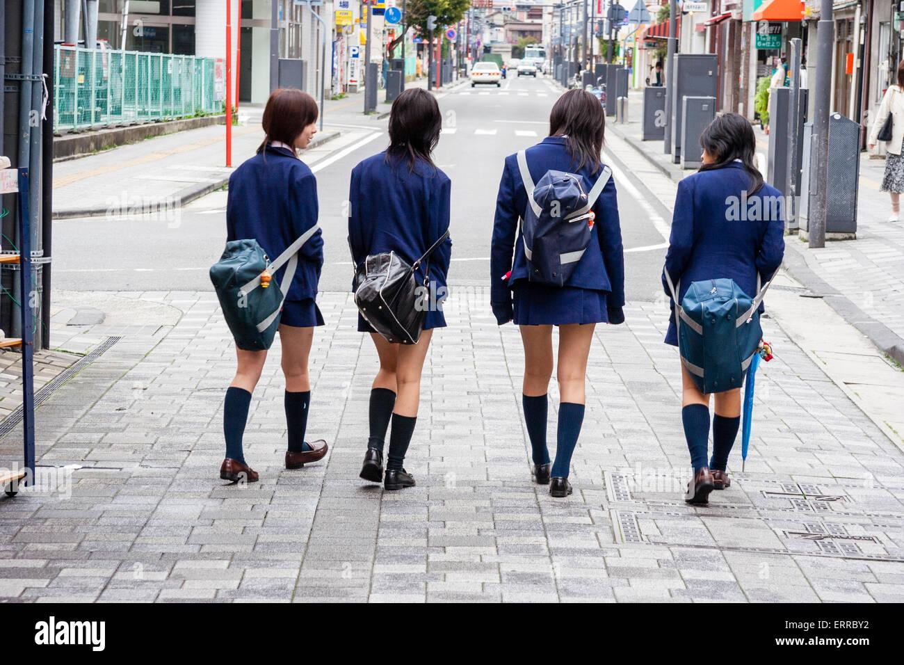 Japan. Line of four Japanese school girls walking away ...
