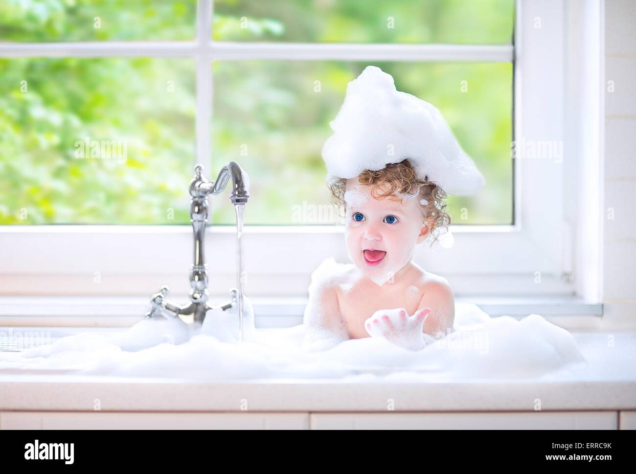 Funny little baby girl with wet curly hair taking bath in a kitchen ...