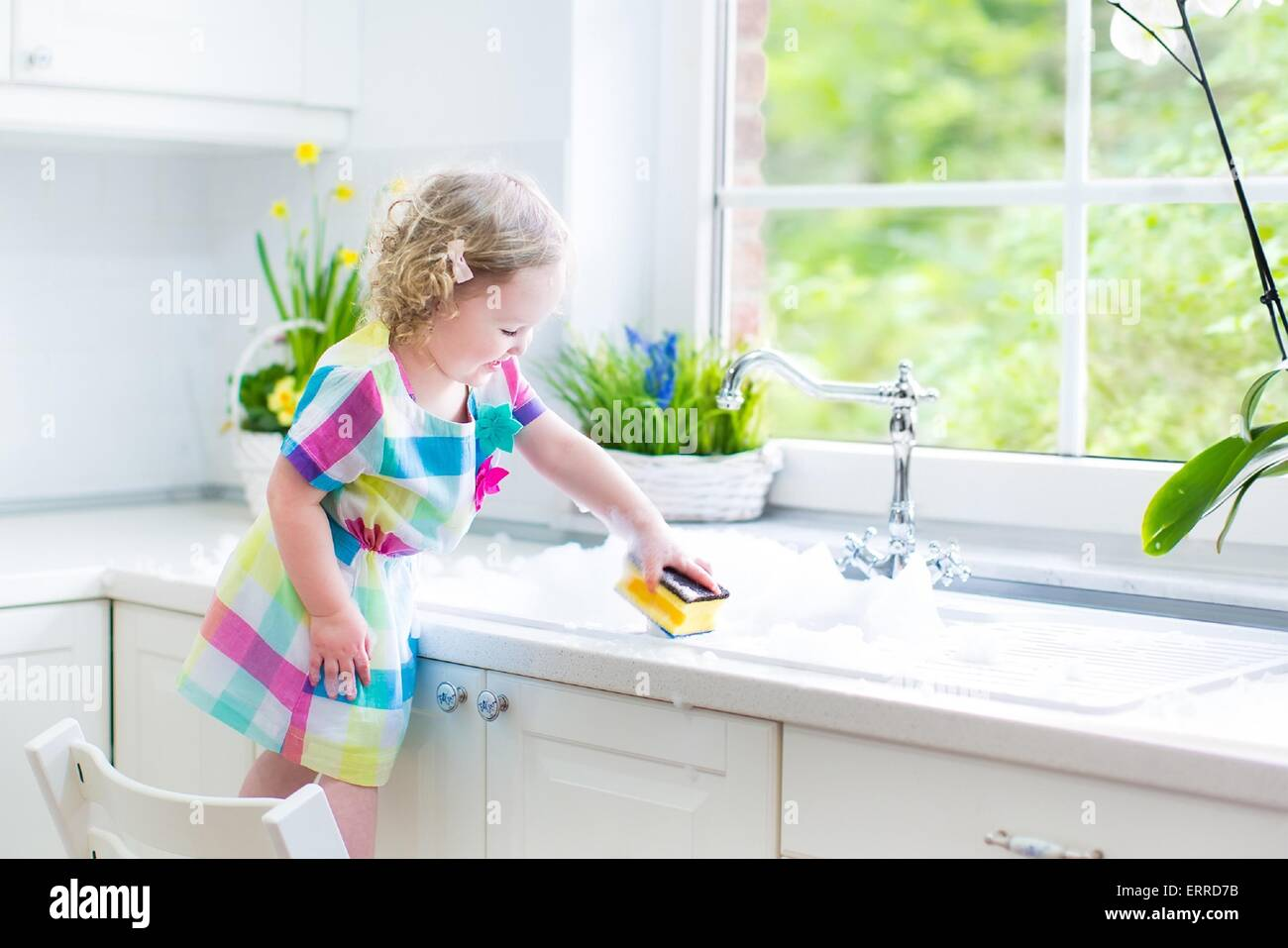 Cute curly toddler girl in a colorful dress washing dishes, cleaning with a sponge and playing with foam in the - Stock Image