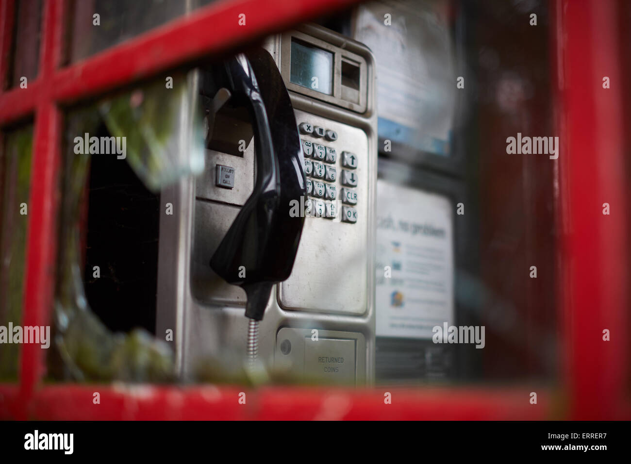 Through the broken window of a red telephone box - Stock Image
