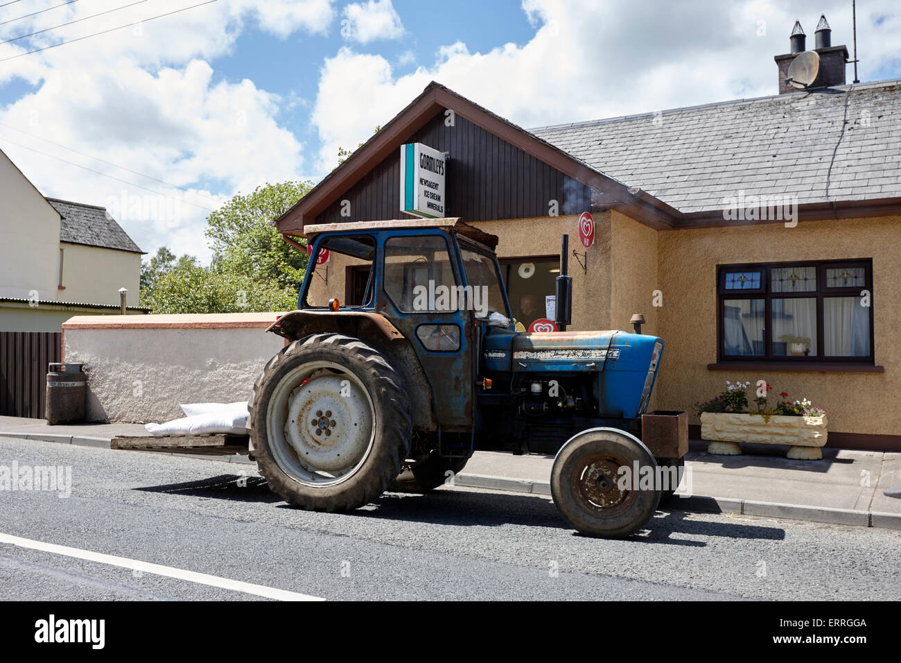 old tractor parked outside a local shop in a small village in rural ireland emyvale monaghan - Stock Image