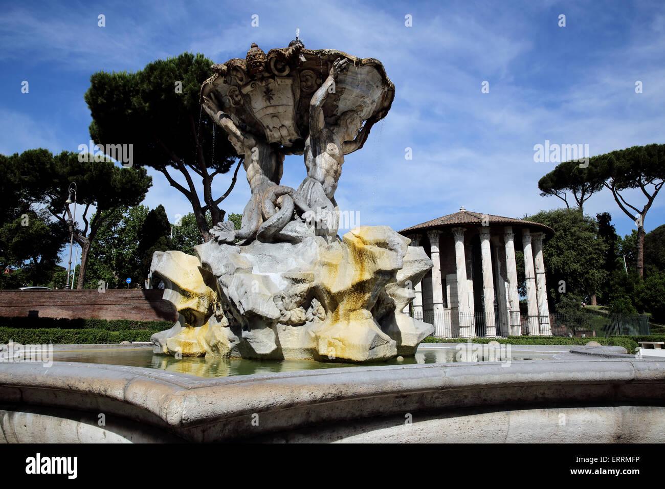 Fountain with Tempio di Ercole Vincitore in the background are part of Forum Boarium in Rome Italy - Stock Image
