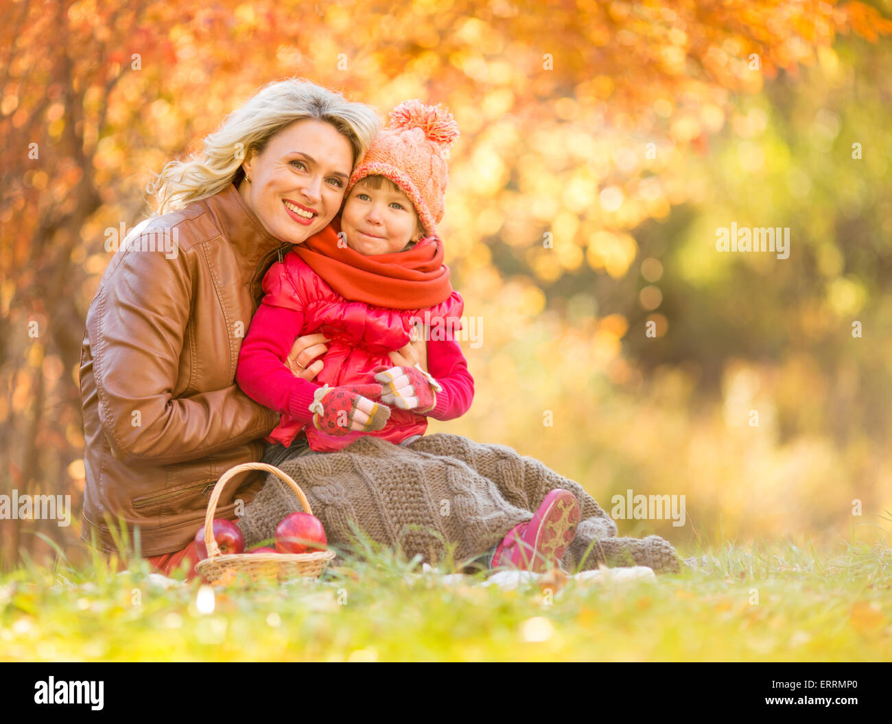 Happy mother and child sitting outdoor in autumn - Stock Image