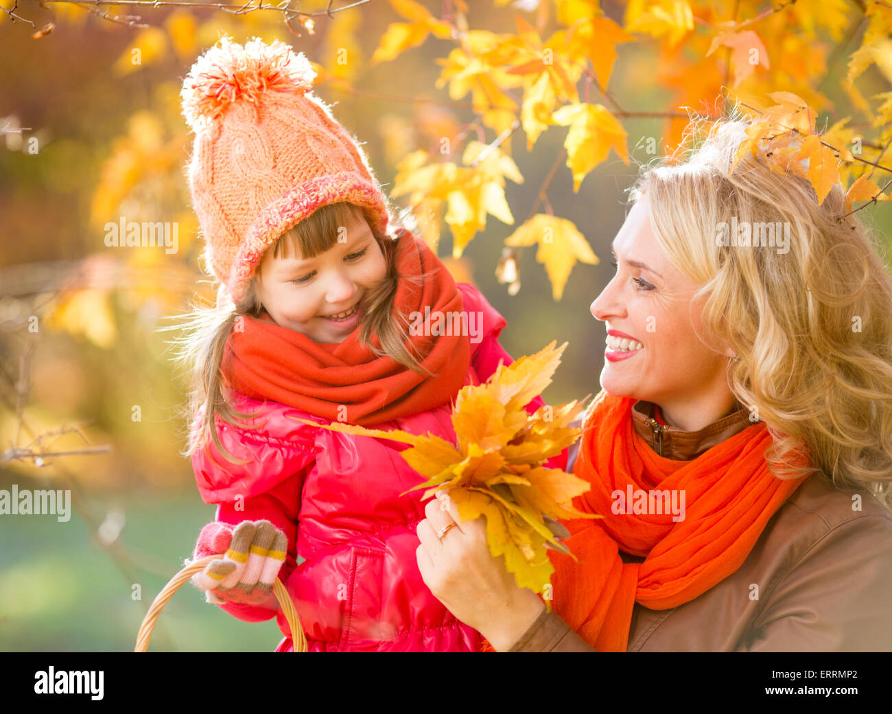 Smiling mother and kid outdoor with autumn yellow leaves - Stock Image